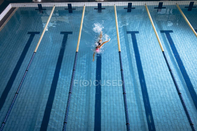 High angle view of a Caucasian woman wearing a swimsuit and a pink swimming cap doing freestyle stroke in the swimming pool — Stock Photo