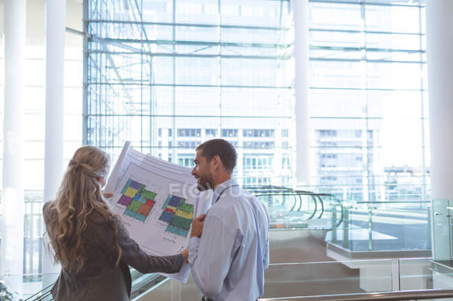 Rear view of business people discussing over blueprint in a modern office building — Stock Photo