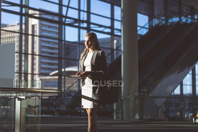Vista laterale della donna d'affari con telefono cellulare in piedi nella hall del moderno edificio per uffici — Foto stock