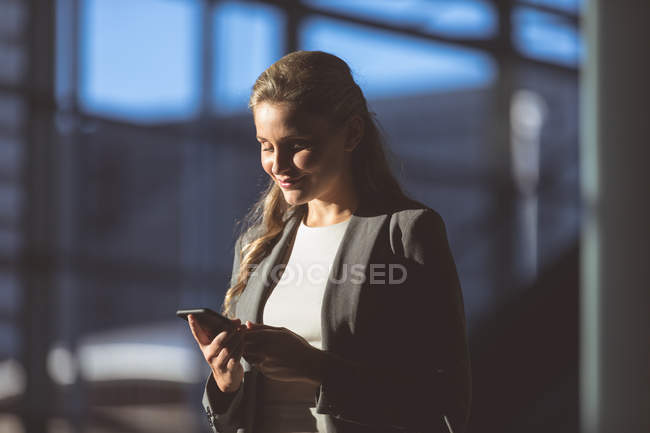 Close-up of businesswoman using mobile phone in lobby at modern office building — Stock Photo