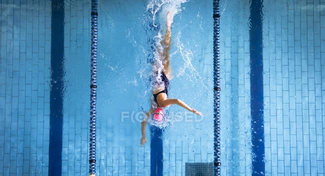 Высокий угол обзора белой женщины в купальнике и розовой плавательной шапке, делающей фристайл-инсульт в бассейне — стоковое фото