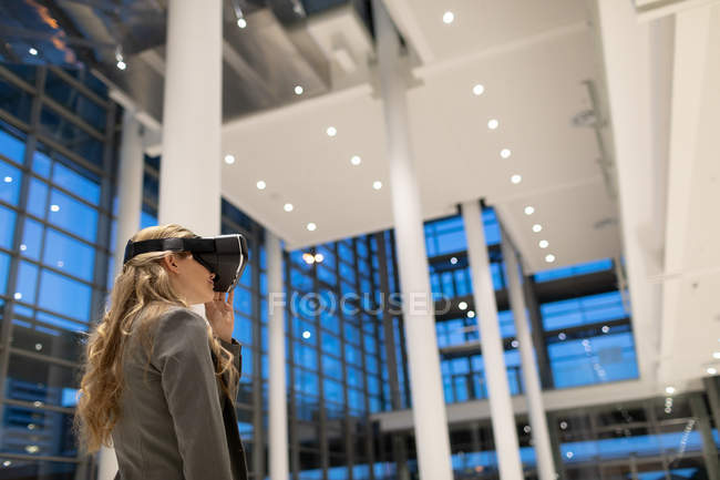 Side view of businesswoman using virtual reality headset in the lobby at modern office — Stock Photo