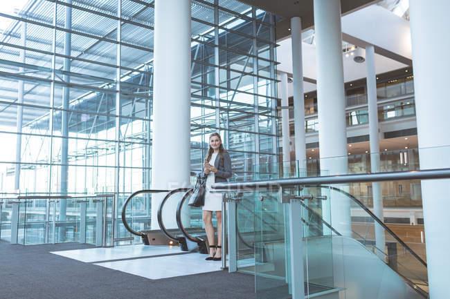 Зовнішній вигляд ділової жінки стоїть біля ескалатора в сучасному офісному корпусі — стокове фото
