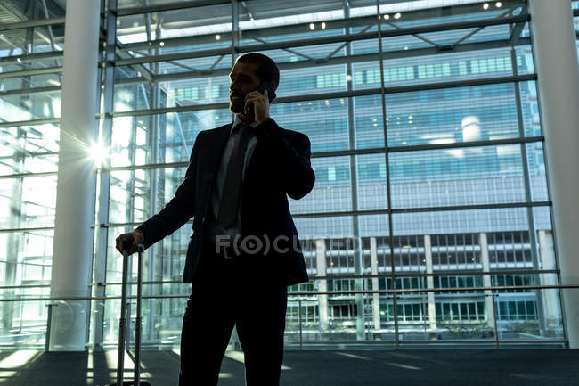 Front view of businessman with trolley bag talking on mobile phone in the modern office building — Stock Photo