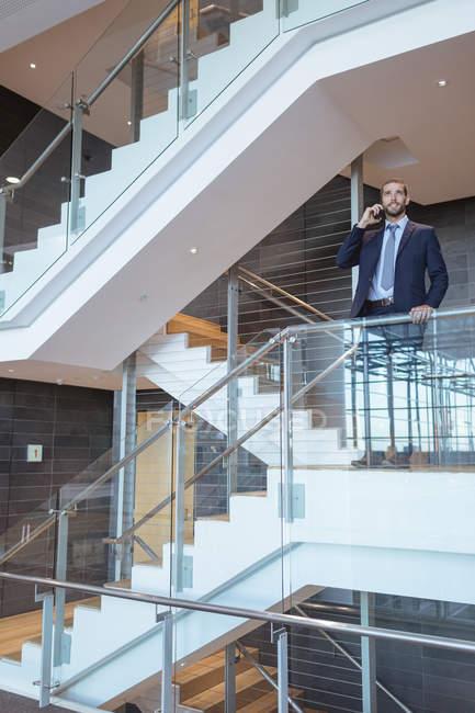 Вид спереди бизнесмена, разговаривающего по мобильному телефону у перил в современном офисном здании — стоковое фото