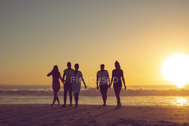 Vorderansicht diverser Freunde, die bei Sonnenuntergang gemeinsam am Strand spazieren gehen — Stockfoto