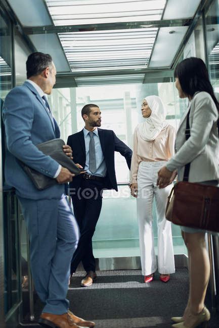 Low angle view of diverse business people using lift in modern office — Stock Photo