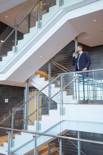Vista frontale dell'uomo d'affari che parla sul telefono cellulare vicino alla ringhiera in un moderno edificio per uffici — Foto stock