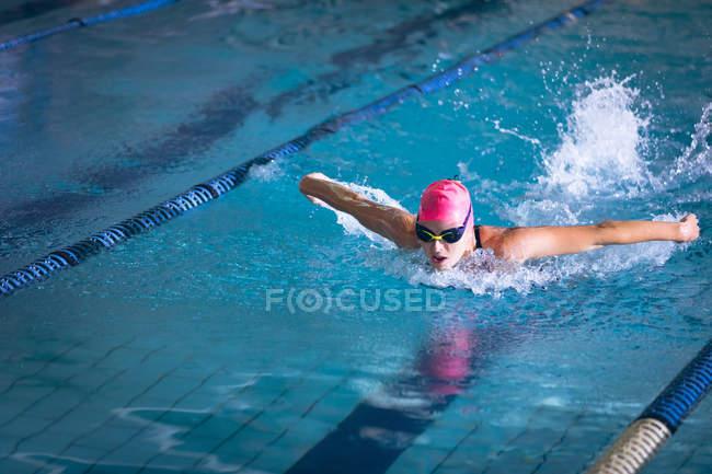 Вид спереди белой женщины в купальнике и розовой плавательной шапочке, делающей инсульт бабочки в бассейне — стоковое фото