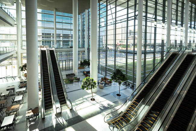 Modern office with windows and escalators in city — Stock Photo