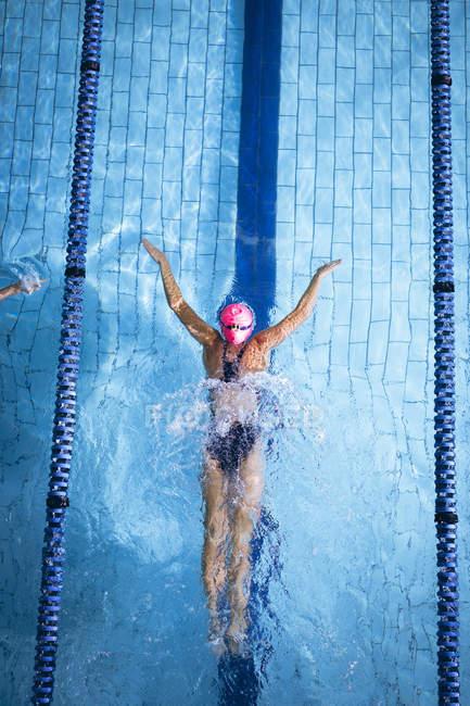 Высокий угол обзора белой женщины в розовой плавательной шапке и очках с инсультом бабочки в бассейне — стоковое фото