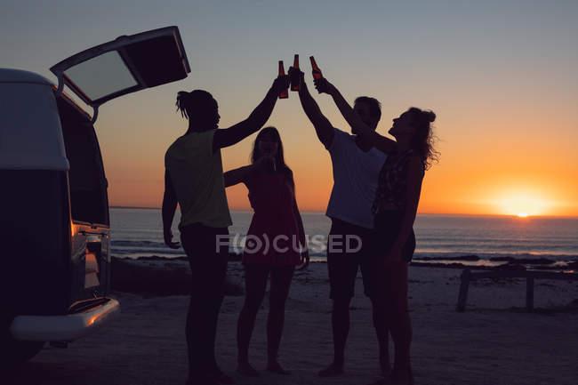 Vue latérale du groupe d'amis divers grillant des bouteilles de bière près du camping-car pendant le coucher du soleil — Photo de stock