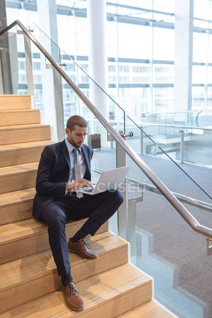 Front view of businessman working on laptop on stairs in a modern office building — Stock Photo