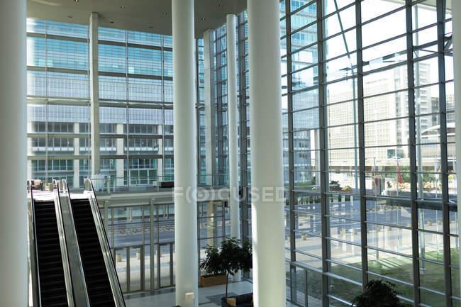 Bureau moderne avec fenêtres et escaliers mécaniques en ville — Photo de stock
