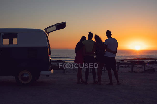 Front view of diverse friends with arms around standing near camper van during sunset — Stock Photo