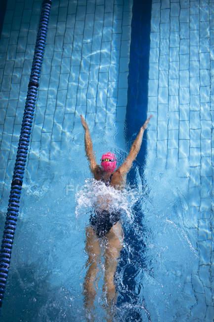 Високий кут зору кавказька жінка носить рожевий кришкою і окуляри робити метелика інсульт в басейні — стокове фото
