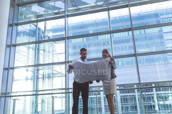 Низкий угол обзора деловых людей, обсуждающих проект в современном офисном здании — стоковое фото