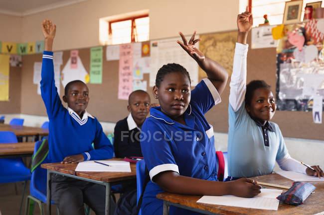 Зовнішній вигляд крупним планом групи молодих африканських школярів сидять на своїх столах, піднявши руки, щоб відповісти на питання під час уроку в містечку початкової школи класі — стокове фото