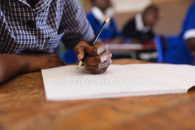 La partie médiane de vue avant d'une jeune écolière s'asseyant à son bureau et écrivant avec un crayon dans son cahier pendant une leçon dans une salle de classe d'école primaire de canton, dans l'arrière-plan ses camarades de classe écrivent également dans leurs livres — Photo de stock