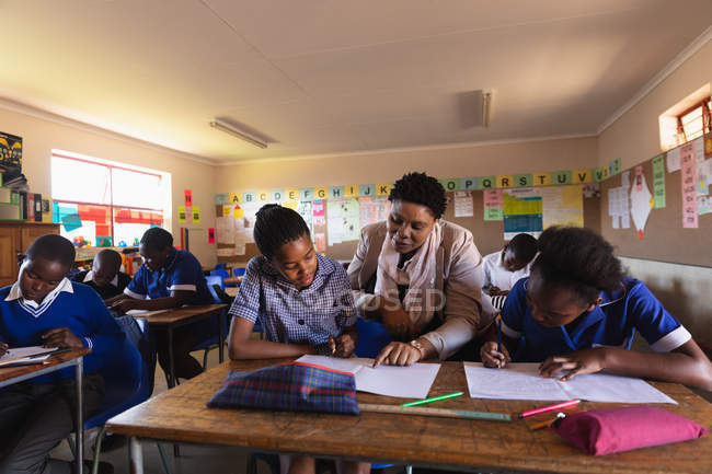 Vista frontale di un'insegnante di scuola africana di mezza età che aiuta una giovane studentessa africana seduta alla sua scrivania durante una lezione in una classe della scuola elementare di township, accanto a lei e in background i compagni di classe stanno scrivendo nei loro libri — Foto stock