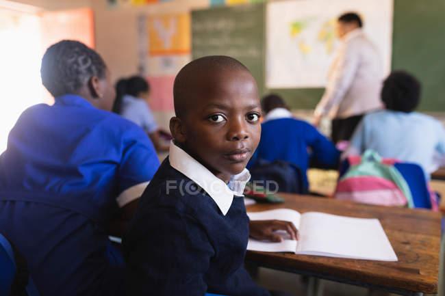 Вид збоку крупним планом молодого Африканського школяр сидить на своєму столі і обертаючи, дивлячись на камеру під час уроку в містечку початкової школи класу. — стокове фото