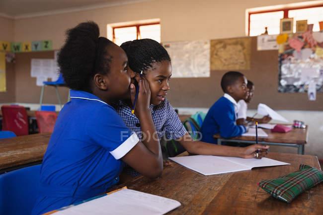 La vue de côté se ferment vers le haut de deux jeunes jeunes écolières africaines s'asseyant à leur bureau chuchotant l'un à l'autre pendant une leçon dans une salle de classe d'école primaire de canton. — Photo de stock