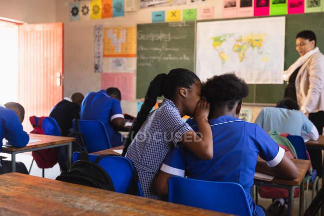 Vista trasera de dos jóvenes colegialas africanas sentadas en su escritorio susurrándose unas a otras durante una lección en un aula de la escuela primaria del municipio . - foto de stock