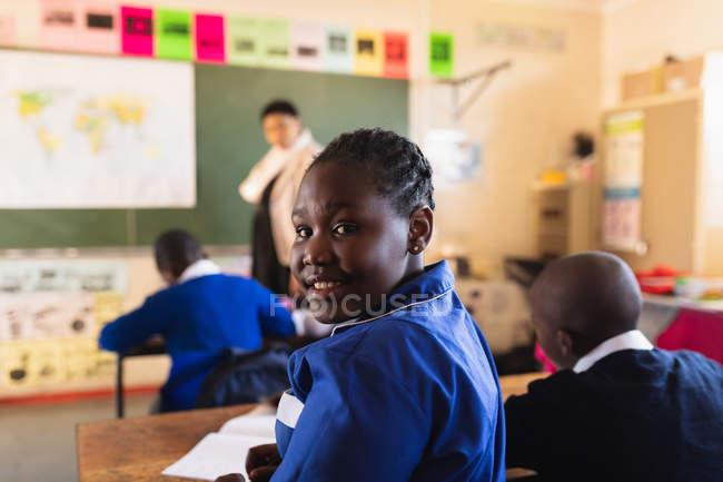 Vue de côté gros plan d'une jeune écolière africaine assise à son bureau et se retournant, regardant vers la caméra et souriant pendant une leçon dans une classe de l'école élémentaire d'un canton . — Photo de stock