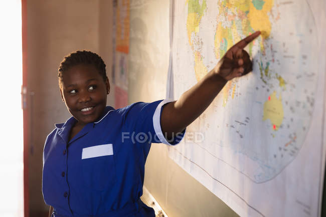 Вид спереду крупним планом молодого Африканського школярки стоячи на передній клас посміхаючись і вказуючи на карту під час уроку в селищі початкової школи класі — стокове фото