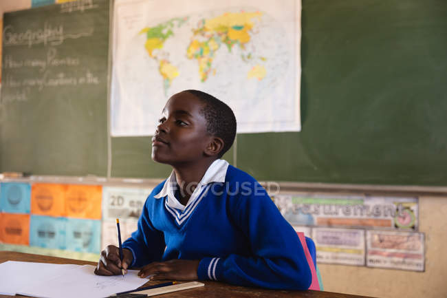 Вид збоку крупним планом молодого Африканського школяр сидить на столі дивлячись під час написання у своїй книзі записки і уважно слухав під час уроку в містечку початкової школи класі — стокове фото