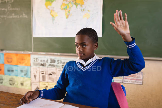 Front view close up of a young African schoolboy sitting at a desk and raising his hand to answer a question during a lesson in a township elementary school classroom, in the background is a world map and the blackboard — Stock Photo