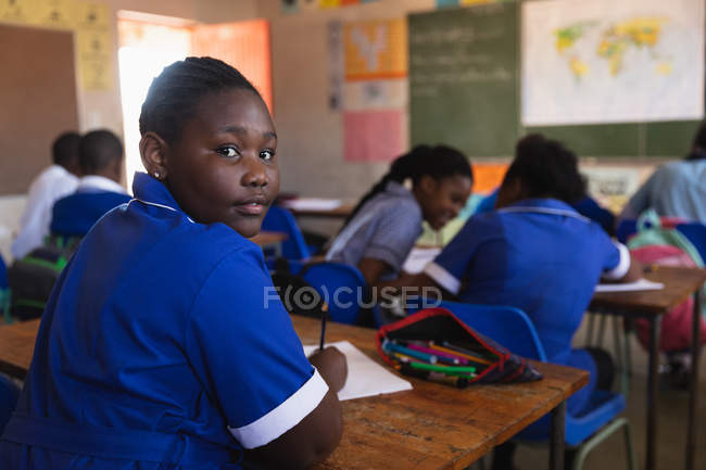 Side view close up of a young African schoolboy sitting at his desk and turning around, looking to camera and smiling during a lesson in a township elementary school classroom. — Stock Photo