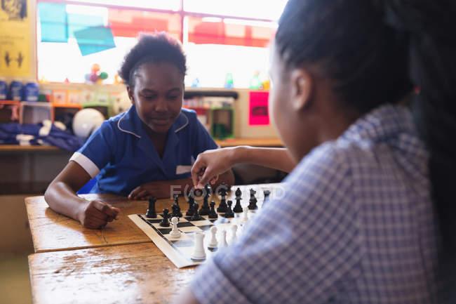 Sopra la vista di due giovani studentesse africane sedute a una scrivania a giocare a scacchi durante una pausa dalle lezioni in una classe della scuola elementare di township — Foto stock