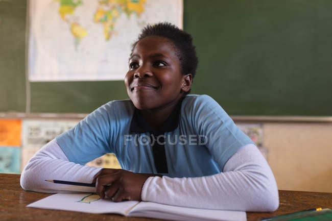 Vista frontal de una joven colegiala africana sentada en un escritorio sonriendo y escuchando atentamente durante una lección en un aula de la escuela primaria del municipio - foto de stock