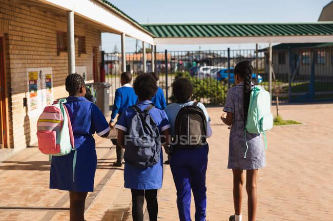 Заднього виду з чотирьох молодих африканських школярок ходьба шкільного двору селища початкової школи несуть свої сумки — стокове фото