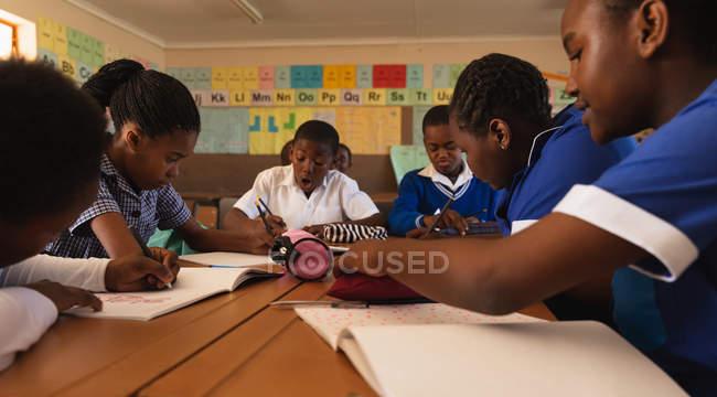Plan d'avis latéral vers le haut d'un groupe de jeunes écoliers africains écrivant dans leurs cahiers pendant une leçon dans une salle de classe d'école primaire de canton — Photo de stock