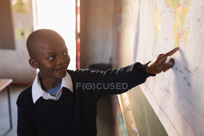 Vue avant vers le haut d'un jeune écolier africain restant à l'avant de la classe souriant et pointant vers une carte pendant une leçon dans une salle de classe d'école primaire de canton — Photo de stock