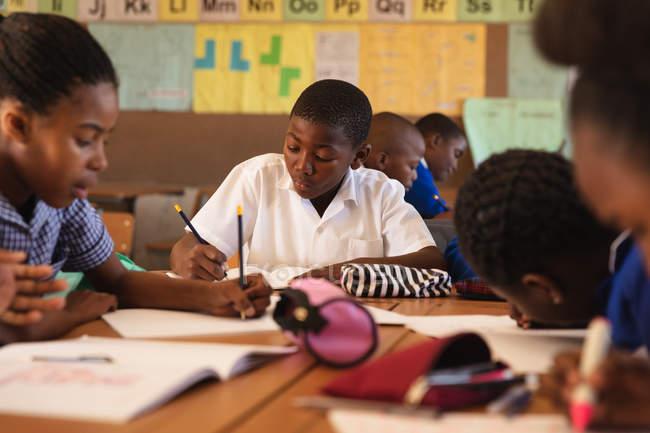 Вид на молодий Африканський школяр сидить на своєму столі письмово під час уроку в селищі початкової школи школі, навколо нього однокласників також сидять на своїх столах письмовій формі — стокове фото