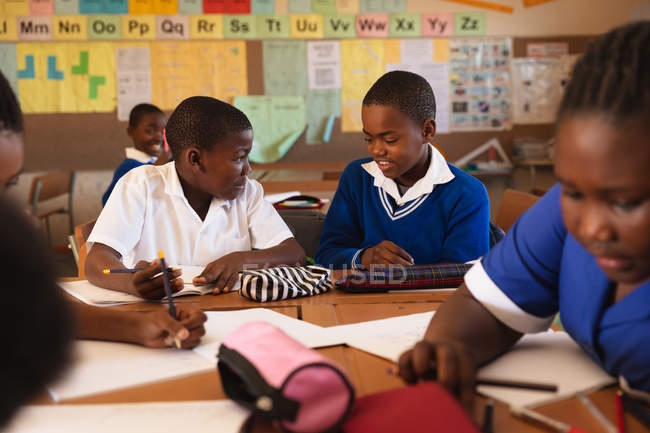 Vue avant de deux jeunes écoliers africains s'asseyant à un bureau écrivant et parlant pendant une leçon dans une salle de classe d'école primaire de canton, autour d'eux camarades de classe sont également assis aux bureaux écrivant — Photo de stock