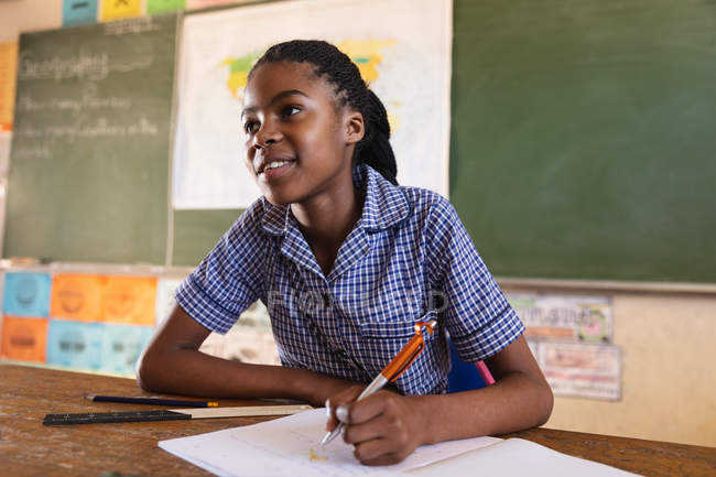 Вид спереду крупним планом молодої африканської школярки сидить на столі посміхаючись, письмово в її записці книгу і уважно слухав під час уроку в селищі початкової школи школі — стокове фото