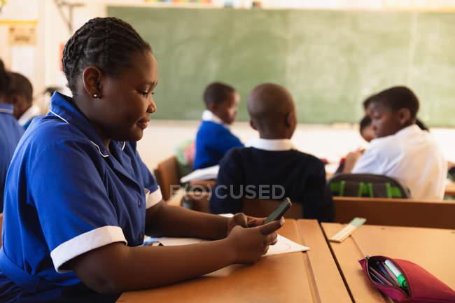 Vista lateral de cerca de una joven colegiala africana sentada en su escritorio usando un teléfono inteligente y sonriendo en un aula en una escuela primaria del municipio . - foto de stock