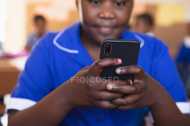 Vista frontal de cerca de una joven colegiala africana sentada en su escritorio usando un teléfono inteligente y sonriendo en un aula en una escuela primaria del municipio, con enfoque en el primer plano . - foto de stock
