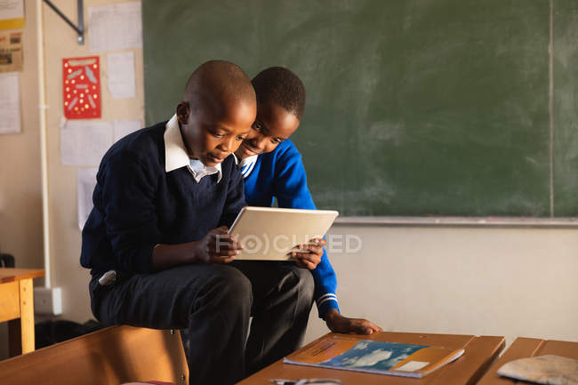 La vue de côté se ferment vers le haut de deux jeunes écoliers africains s'asseyant sur les dos des chaises regardant un ordinateur de tablette pendant une pause des leçons dans une salle de classe d'école primaire de canton — Photo de stock