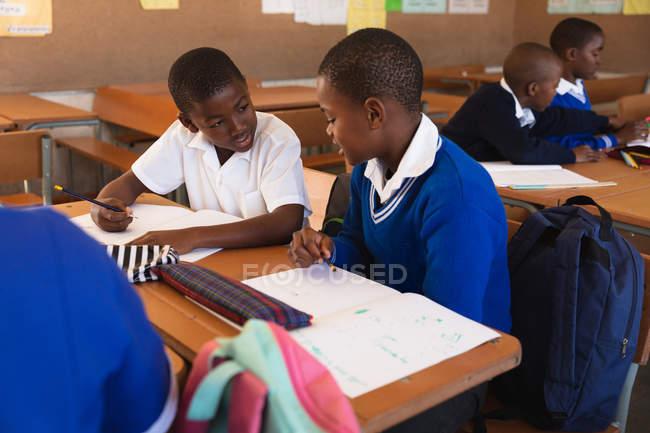 La vue avant vers le haut de deux jeunes écoliers africains s'asseyant à un bureau écrivant et parlant pendant une leçon dans une salle de classe d'école primaire de canton, dans les camarades de classe de fond sont également assis aux bureaux écrivant — Photo de stock