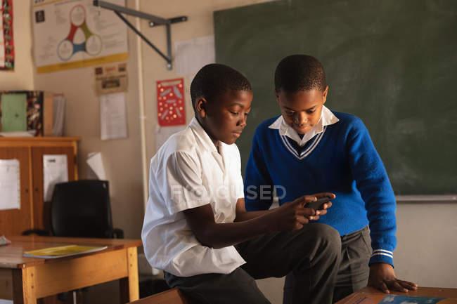 Vista laterale da vicino di due giovani scolari africani che guardano uno smartphone durante una pausa dalle lezioni in una classe della scuola elementare di township — Foto stock