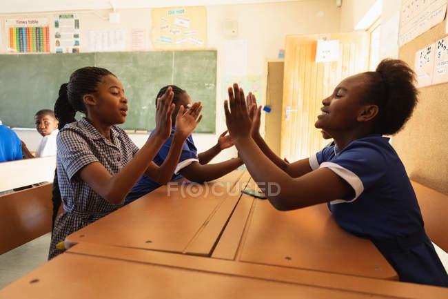 Vista laterale da vicino di due giovani studentesse africane sedute a scrivania a giocare a un gioco di applausi e cantare durante una pausa dalle lezioni in una classe della scuola elementare di township, sullo sfondo altre due ragazze stanno anche giocando insieme — Foto stock