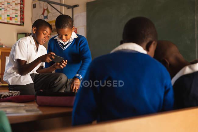 Vista frontale di due giovani scolari africani che guardano uno smartphone durante una pausa dalle lezioni in una scuola elementare township, in primo piano la vista posteriore di altri due ragazzi guardando anche qualcosa insieme — Foto stock
