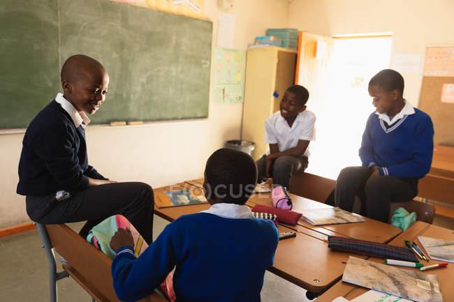 Vue élevée de quatre jeunes écoliers africains s'asseyant autour d'un bureau parlant pendant une pause des leçons dans une salle de classe primaire de canton, trois d'entre eux sont assis sur les dos des chaises — Photo de stock