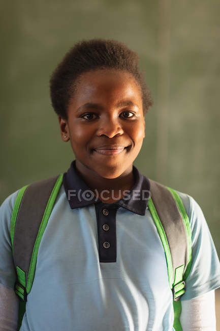 Retrato de cerca de una joven colegiala africana con su uniforme escolar y su mochila, mirando directamente a la cámara sonriendo, en una escuela primaria del municipio - foto de stock