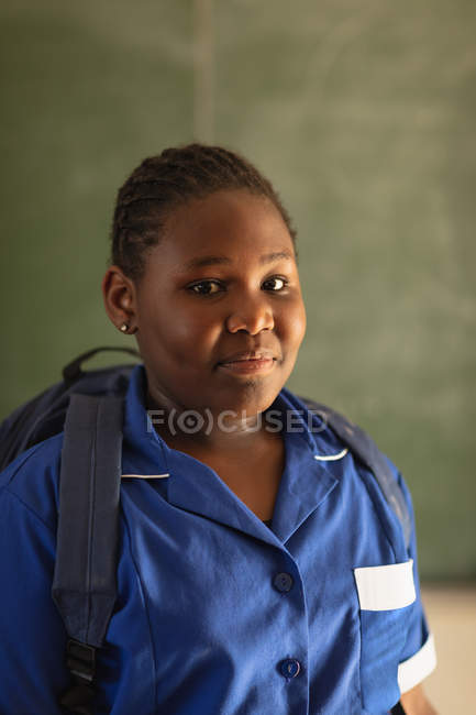 Portrait close up of a young African schoolgirl wearing her school uniform and schoolbag, looking straight to camera smiling, at a township elementary school — Stock Photo